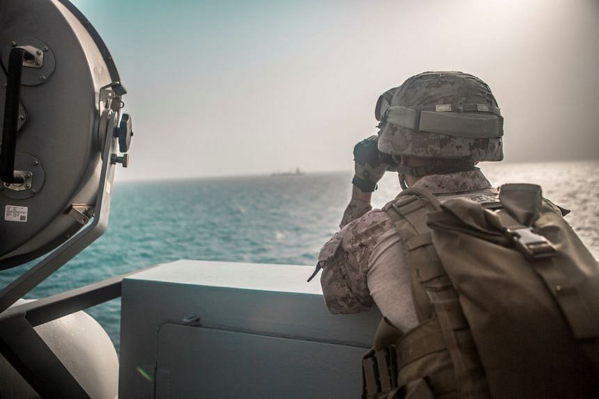 A US Marine ranges nearby boats from aboard the USS John P. Murtha during a Strait of Hormuz transit in July 2019.