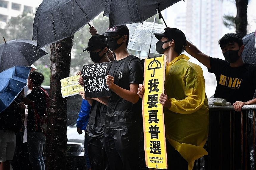 People braving the rain outside the Eastern Magistrates' Court in Hong Kong to show support for those charged yesterday. Hong Kong has been hit by eight straight weeks of mass protests sparked by the now-suspended extradition Bill. A man trying to sh