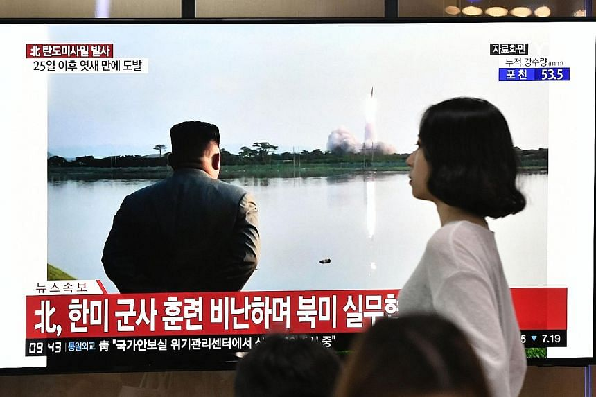 A television set at a railway station in Seoul yesterday broadcasting file footage of North Korean leader Kim Jong-un watching a missile launch.
