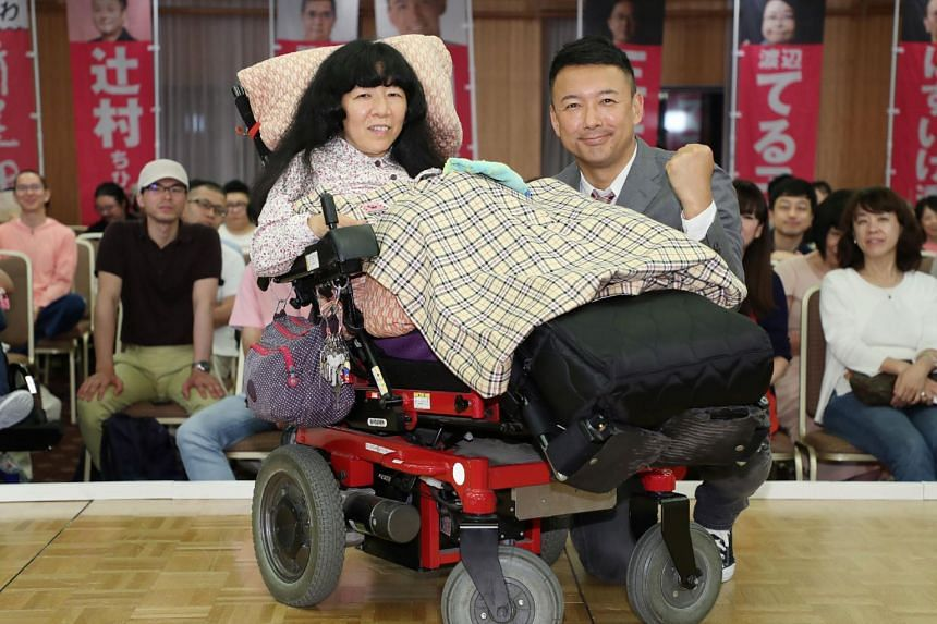 Ms Eiko Kimura and Upper House member Taro Yamamoto celebrate her win in the election in Tokyo, on July 22, 2019.