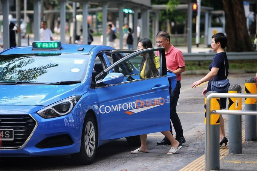 A Comfort Delgro taxi picking up passengers at a taxi stand.