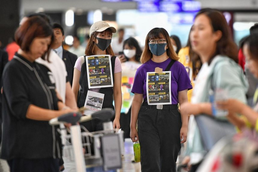 Protesters walking around Hong Kong's airport on July 30, 2019, spreading the message of the anti-extradition Bill movement to foreigners visiting the city.