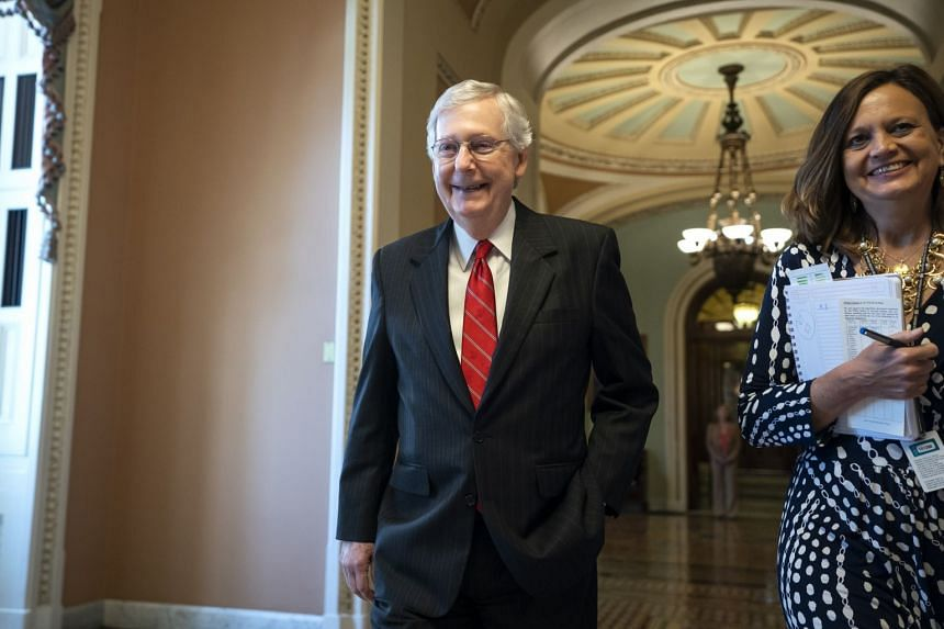 Senate Majority Leader Mitch McConnell walks off the Senate floor after the Bill's passage.