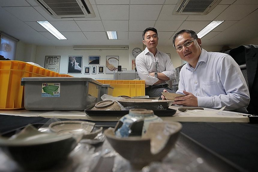 Dr Terence Chong (left), head of the Temasek History Research Centre, and archaeologist Tai Yew Seng, a visiting fellow at the centre, with artefacts from the Empress Place excavation. The centre will get $400,000 a year from the Temasek Foundation f