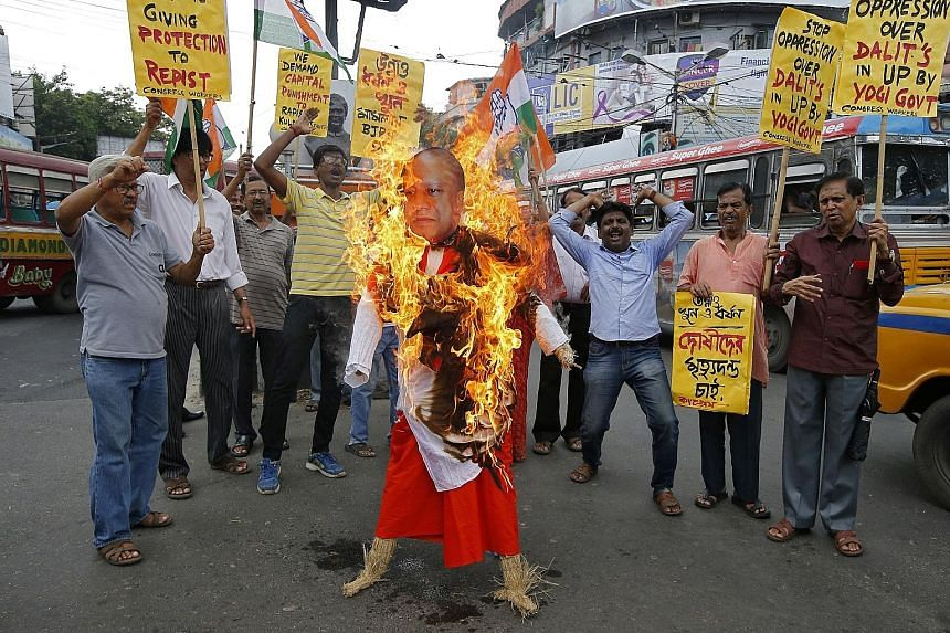 Protesters in Kolkata crowding around a burning effigy depicting Uttar Pradesh Chief Minister Yogi Adityanath, demanding justice for the teen who is fighting a rape case against a legislator of the ruling BJP.