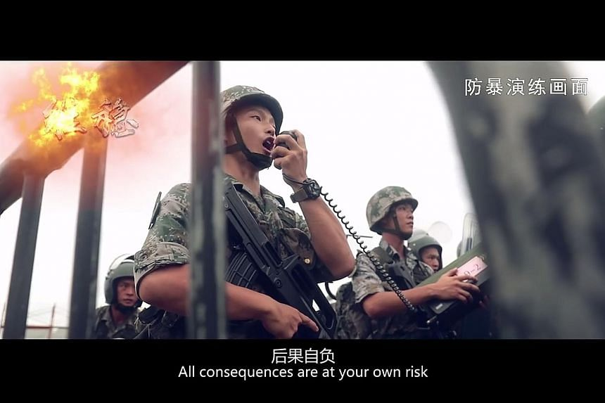 """Screengrabs (from top) showing PLA soldiers issuing a warning to """"protesters"""" during an """"anti-riot"""" drill, troops advancing as they fire rifles into the air, and """"protesters"""" being detained by PLA soldiers. The three-minute video was posted on the Ho"""