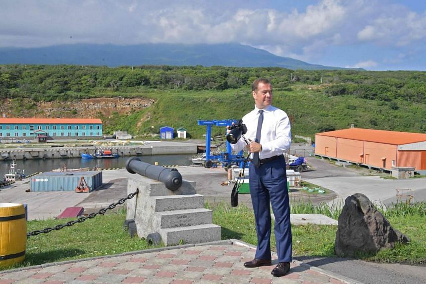Russian Prime Minister Dmitry Medvedev takes pictures while visiting Iturup island, one of four islands in the disputed chain known as the Kuril Islands in Russia and the Northern Territories in Japan, on Aug 2, 2019.