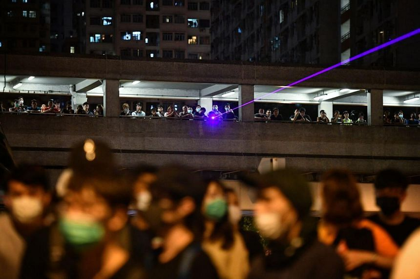 Protesters use laser pointers to target the policemen even as hundreds of them surround the Kwai Chung Police Station on July 30, 2019.