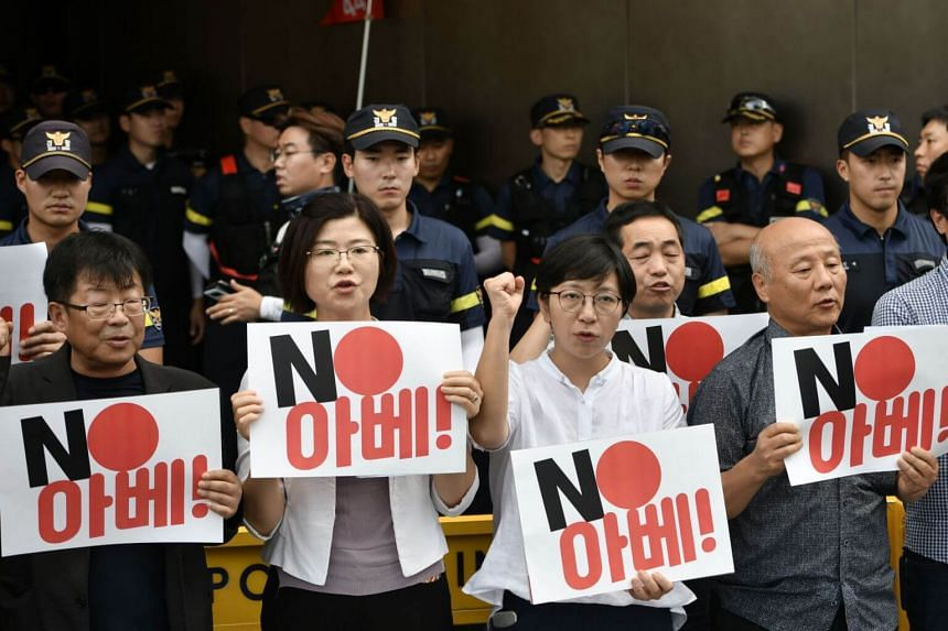 """South Korean protestors hold placards reading """"No Abe!"""" during a rally against Japan's decision to remove South Korea from a so-called white list of favoured export partners, in front of the Japanese embassy in Seoul on Aug 2, 2019."""