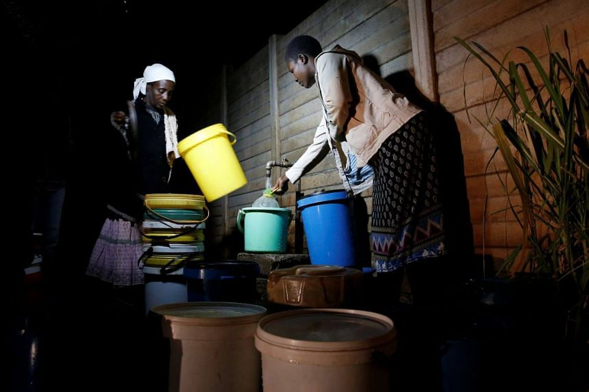 Residents collect water at night from an electric-powered borehole, as the country faces 18-hour daily power cuts, in a suburb of Harare, Zimbabwe, on July 30, 2019.