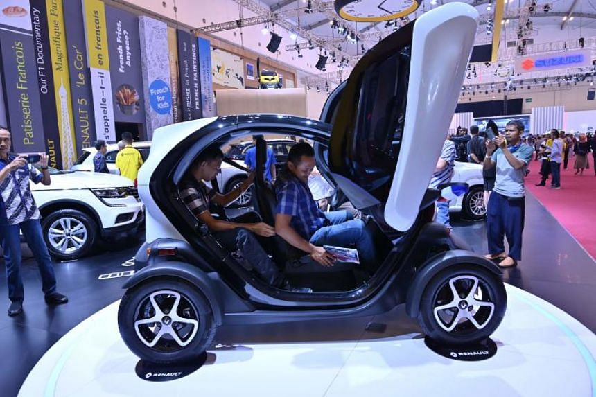Visitors taking a look at the Twizy electric car by French carmaker Renault on display at the Gaikindo Indonesia International Auto Show in Tangerang, Banten province, on July 25, 2019.