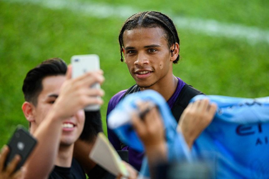 Sane (centre) takes a selfie with a fan after a team training session in Hong Kong in July 2019.