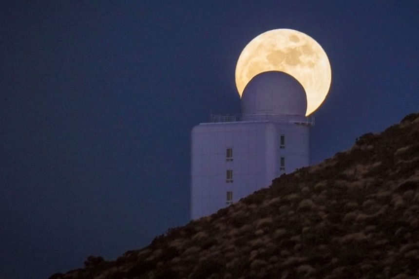 A full moon passes behind a telescope at Spain's Institute of Astrophysics in the Canary Islands.