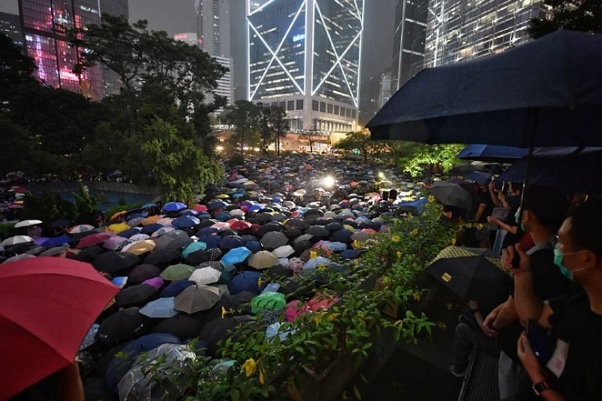 A crowd gathers to watch the civil servant protest from the roof of Chater Garden on Aug 2, 2019.