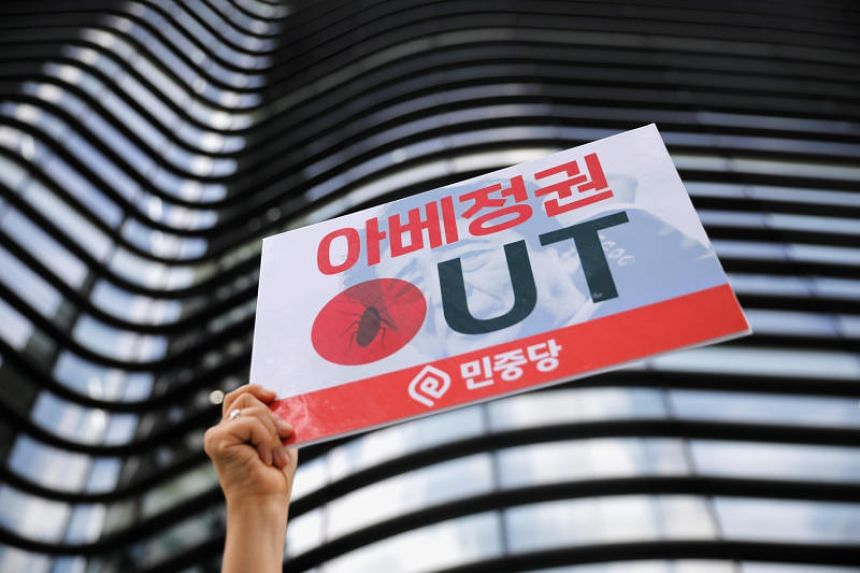"""A protester holds up a sign reading """"Abe regime out"""" during an anti-Japan rally in front of the Japanese embassy in Seoul on Aug 2, 2019."""