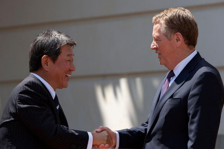 Japanese Economy Minister Toshimitsu Motegi and US Trade Representative Robert Lighthizer shake hands prior to negotiations at the Office of the United States Trade Representative in Washington on Aug 1, 2019.