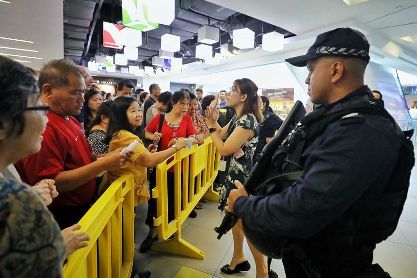 People being held back from the Huawei store at NEX shopping mall in Serangoon on July 26, 2019.