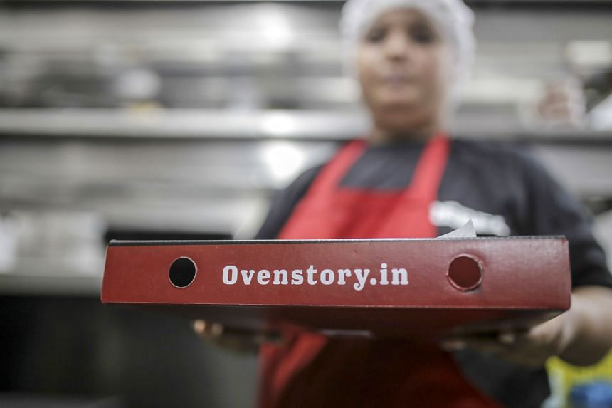 Employees preparing orders (left) at a Rebel Foods cloud kitchen in the Indian city of Mumbai. The company serves a dozen different menus with everything from cheese-loaded Italian pizzas (above) to 99 variations of the dosa, a lentil-and-rice crepe.