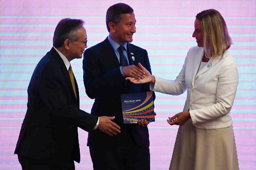 EU foreign policy chief Federica Mogherini (right) receives a book from Dr Balakrishnan (centre), as Thailand's Foreign Minister Don Pramudwinai looks on, during the meeting in Bangkok.