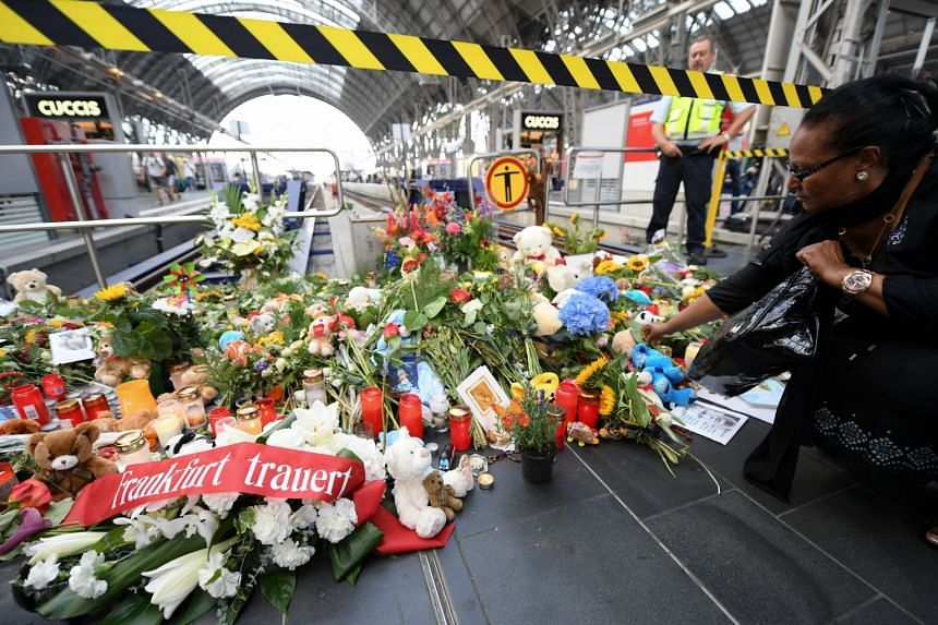 A woman lays flowers on Platform 7 at Frankfurt Central Station, where an eight-year-old boy was pushed in front of a train.