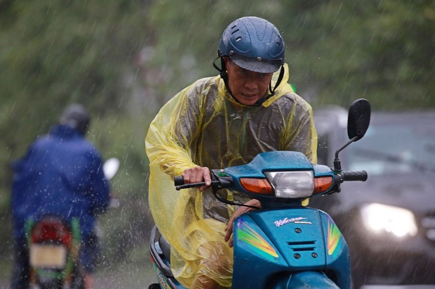 A man rides a motorbike in heavy rain caused by tropical storm Wipha, in Hanoi, Vietnam.