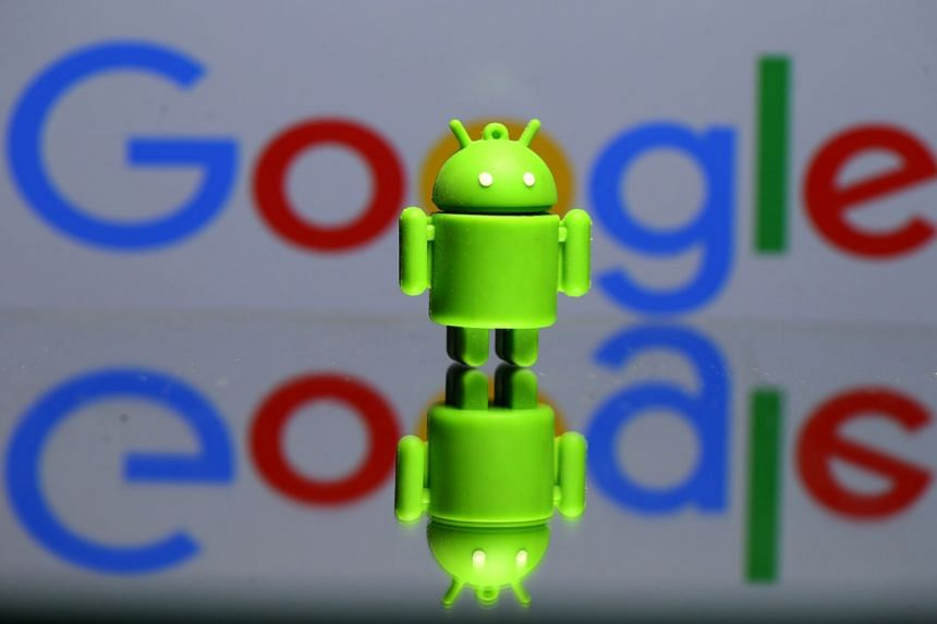 A 3D printed Android mascot, Bugdroid, is seen in front of Google's logo in this illustration.