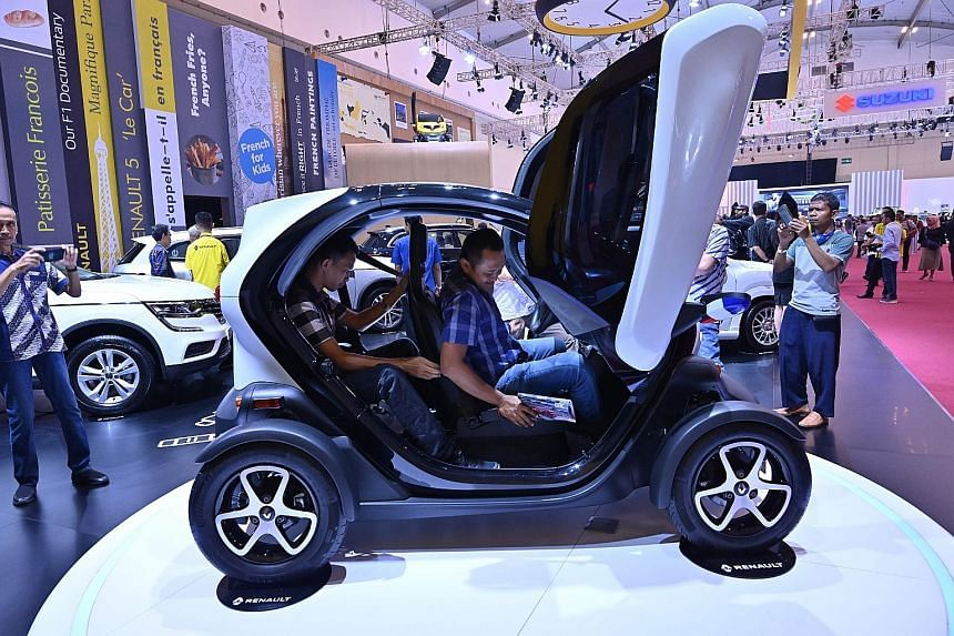 Visitors checking out an electric car by French firm Renault at a trade show in Indonesia's Banten province last month. According to a draft Indonesian government strategy, under new rules, electric-car makers will have to gradually increase the amou