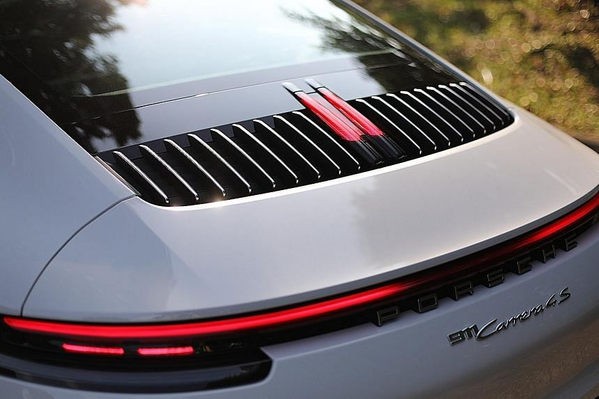 The Porsche 911's iconic front remains largely unchanged, but the rear is adorned with ultra-slim tail-lamp clusters joined by an LED strip. A brake light sits amid vertical louvres which form a nice relief between the rear windscreen and the rear sp
