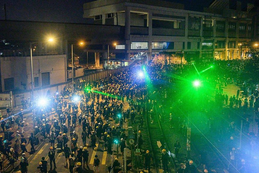 Protesters using lasers outside Yuen Long MTR station last Saturday. Many of the protesters' lasers are focused on police surveillance cameras to stop themselves from being easily identified. Riot police have also used high-powered beams to confuse p