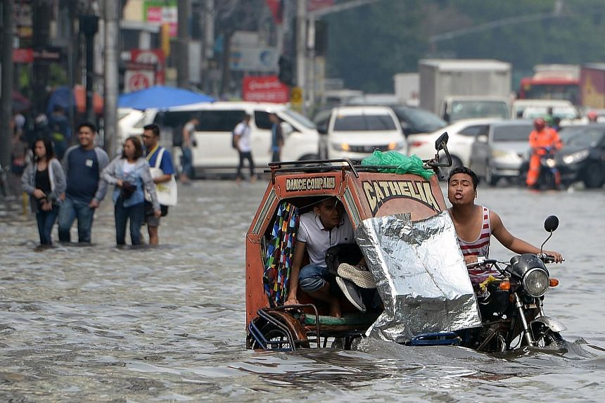 Residents riding through a flooded street in Manila yesterday following heavy rain brought about by a south-west monsoon. PHOTO: AGENCE FRANCE-PRESSE