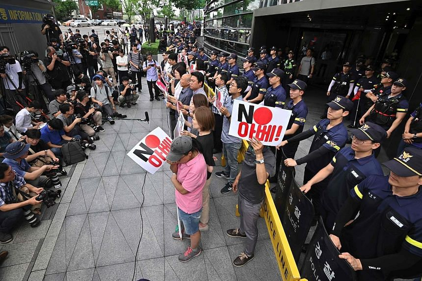 """Protesters outside the Japanese Embassy in Seoul yesterday, with signs that read """"No Abe"""", referring to Japanese Prime Minister Shinzo Abe. PHOTO: AGENCE FRANCE-PRESSE"""