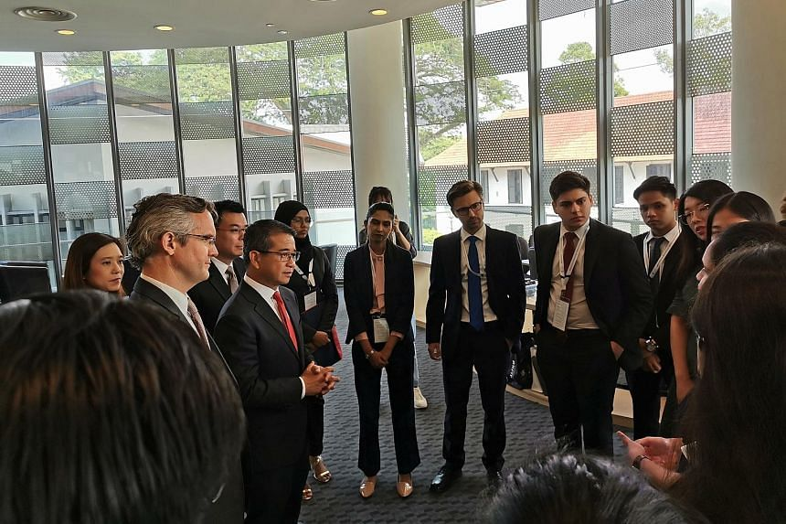 Senior Minister of State for Law and Health Edwin Tong (with red tie), with National University of Singapore (NUS) law dean Simon Chesterman (at far left) and Ministry of Law Deputy Secretary Han Kok Juan (behind Mr Tong), interacting with internatio