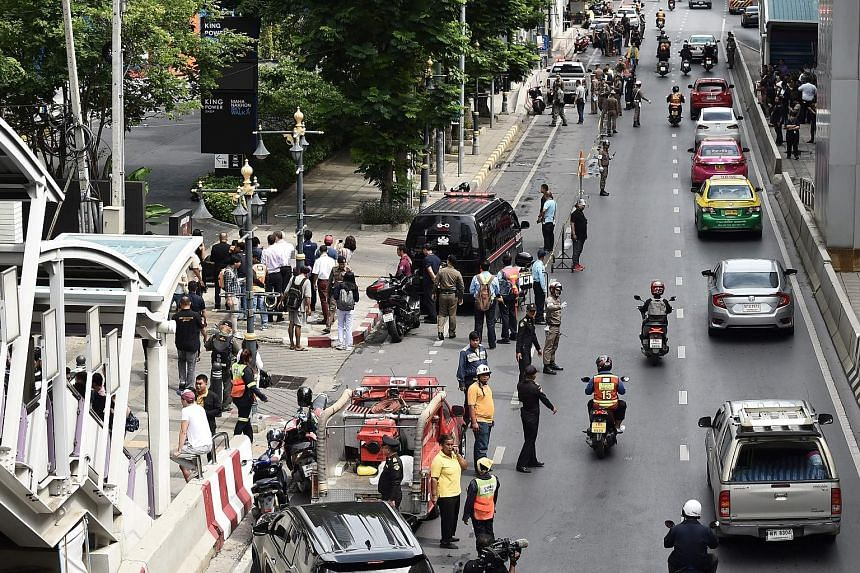 Above: Thai bomb squad officers checking a site in Rama 9 Road where a bomb exploded. The police said the explosion there injured at least two street sweepers. Left: Onlookers and the police at the scene of an explosion in Bangkok yesterday. Homemade