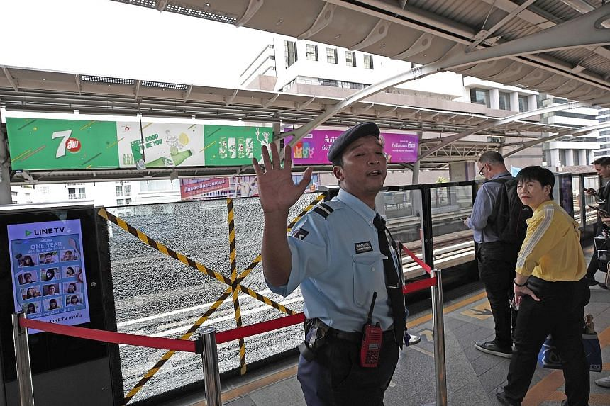 A security officer guarding a shattered platform door at the Bangkok skytrain station near where a small bomb exploded yesterday morning during rush hour, sending commuters fleeing. PHOTO: EPA-EFE