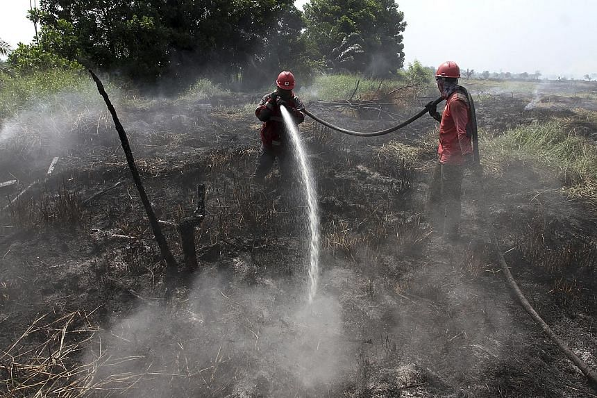 The Petronas Twin Towers and KL Tower in Kuala Lumpur shrouded in haze on Thursday morning as a result of fires in Indonesia's Riau province. PHOTO: BERNAMA Firefighters battling a wildfire in Indonesia's Riau province on Thursday. The fires have led
