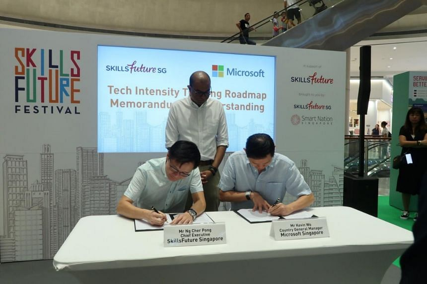Dr Janil Puthucheary, Senior Minister of State for Transport as well as Communications and Information, witnessing the signing of a memorandum of understanding between SkillsFuture Singapore chief executive Ng Cher Pong and Microsoft Singapore managi