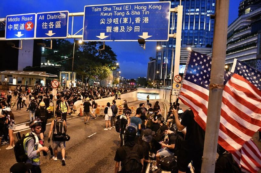 Protesters block a road outside InterContinental Hong Kong in Tsim Sha Tsui district on Aug 3, 2019.