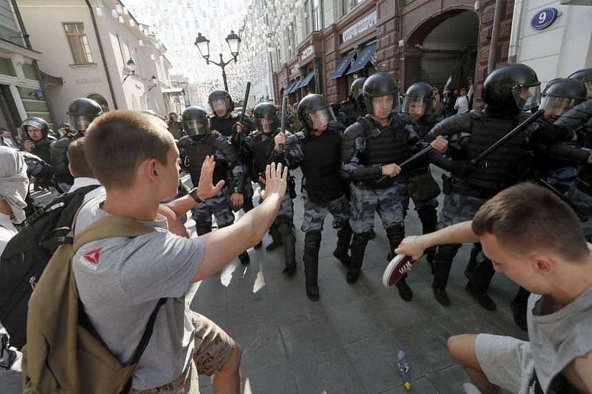 Russian riot police disperse opposition activists during a protest in the centre of Moscow, on July 27, 2019.