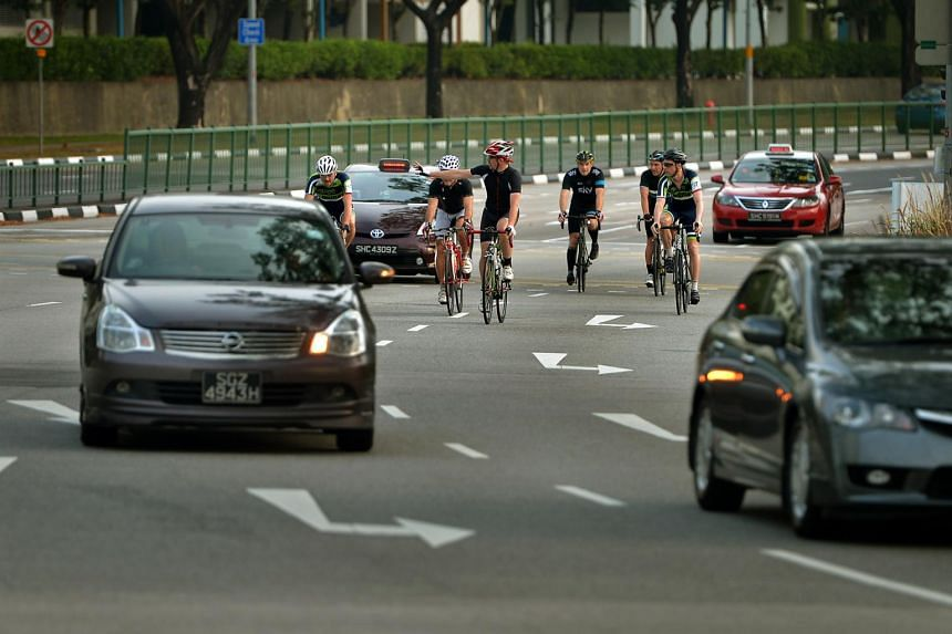 A group of cyclists riding along Sengkang East Drive attempting to filter across two lanes.