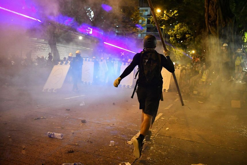Protesters retreat as tear gas is fired.