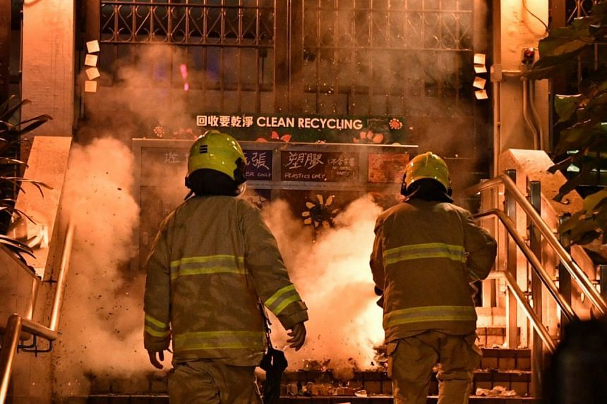 Firefighters tackle a blaze after protesters set fire to a police station gate.