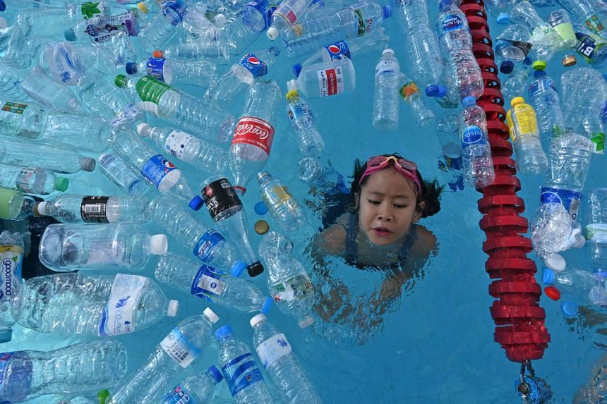 A child swims in a pool filled with plastic bottles during an awareness campaign to mark World Oceans Day in Bangkok.