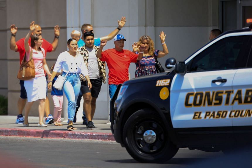 Shoppers exit with their hands up after a mass shooting at a Walmart in El Paso, Texas.
