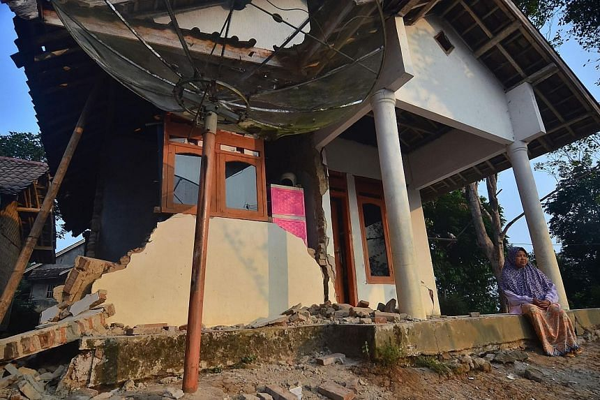 A survivor outside a house in Pandeglang that was damaged by the 6.9-magnitude earthquake that rocked Indonesia's Java island on Friday night. The quake killed at least five people and injured four others. PHOTOS: AGENCE FRANCE-PRESSE