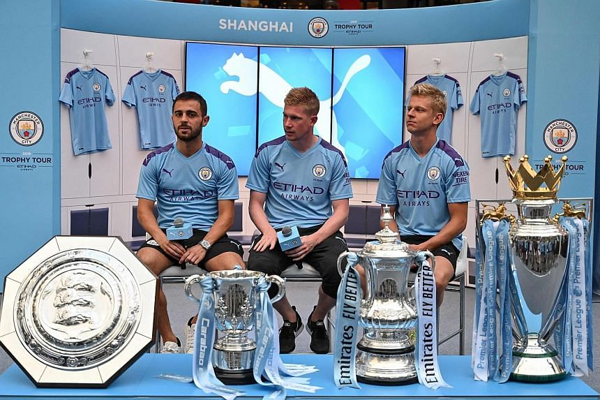 Manchester City players (from far left) Bernardo Silva, Kevin de Bruyne and Oleksandr Zinchenko with the club's four trophies won last season - Community Shield, League Cup, FA Cup and English Premier League. They were at a promotional event in Shanghai o