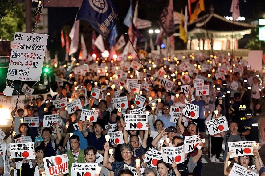 South Koreans holding a candlelight vigil in front of the Japanese Embassy in Seoul yesterday over the two sides' ongoing trade feud.