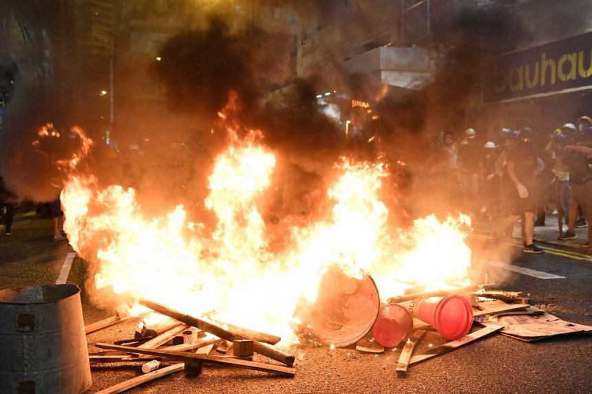 Protesters setting fire to a roadblock at Causeway Bay to prevent police from advancing, on Aug 4, 2019.