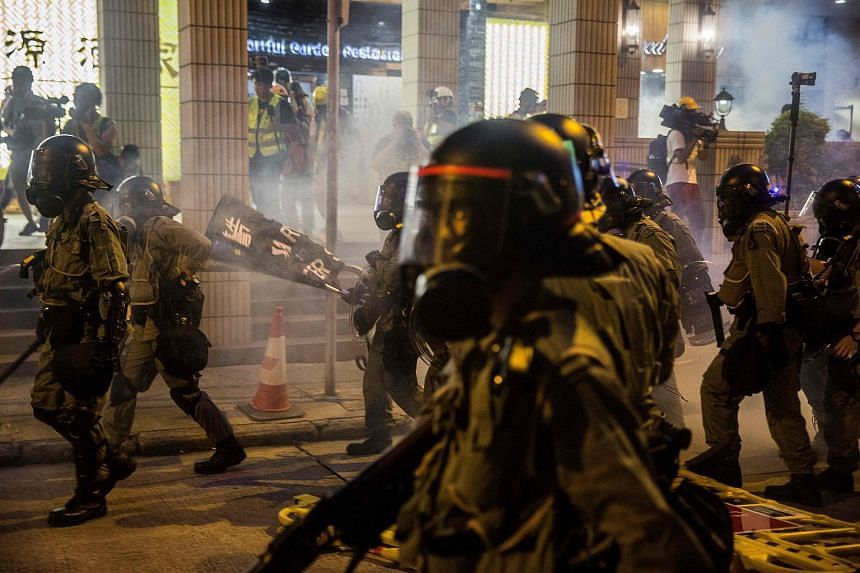 Riot police advancing through clouds of tear gas in a bid to disperse protesters, in Hong Kong on Aug 4, 2019.