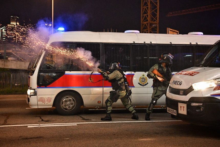 A police officer firing a tear gas round at protesters while retreating towards police vehicles, on Aug 4, 2019.