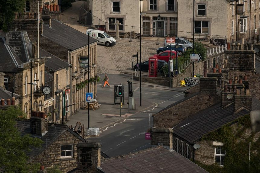 A member of the emergency services walking through the deserted city centre of Whaley Bridge, in Derbyshire, after the city was evacuated over fears of a collapsing dam, on Aug 4, 2019.